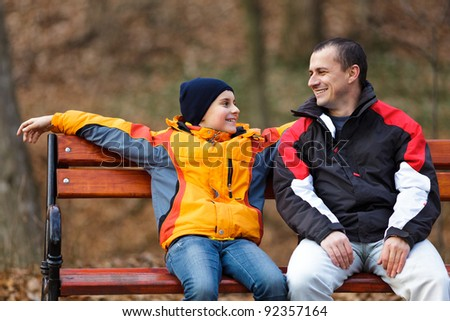 Father and son sitting on a bench and talking