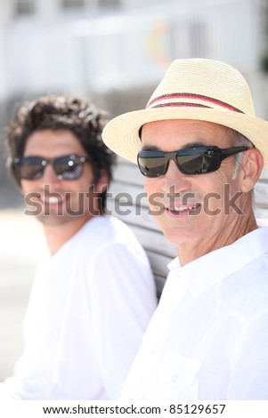 Father and son sitting on a bench together on a sunny day - stock photo