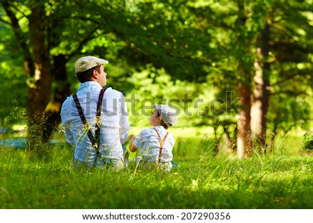 father and son sitting on forest lawn - stock photo