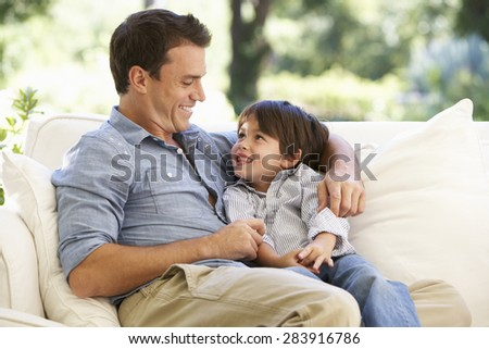 Father And Son Sitting On Sofa At Home - stock photo