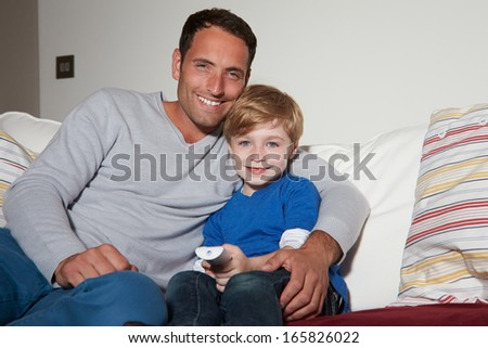 Father And Son Sitting On Sofa Watching TV Together - stock photo