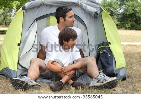 Father and son sitting outside a tent - stock photo