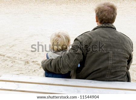 Father and son sitting together. - stock photo