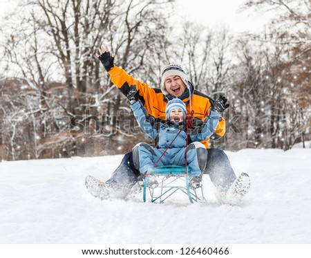 Father and son sledding at winter time