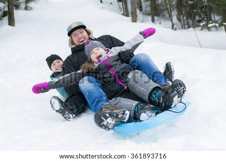 Father and son sledding at winter time - stock photo