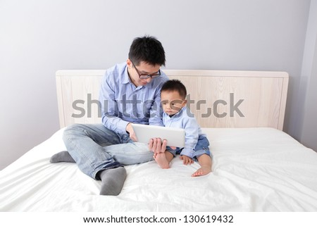 Father and son smile and happy using tablet pc on bed at home, asian people - stock photo