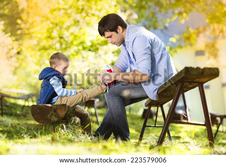 Father and son spending time together in summer nature, little boy is tying his father's shoes - stock photo