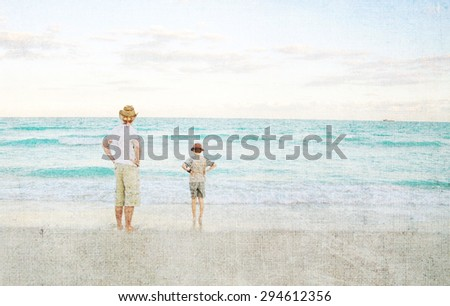 Father and son standing in water on an ocean beach, looking out to the horizon.  Both have their hand on hips and wear a hat.  The late afternoon sun and texture add a vintage flare.
