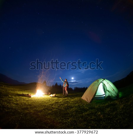 Father and son standing near big campfire and tent looking at beautiful night sky full of stars and enjoying night scene. Man is pointing at the sky - stock photo