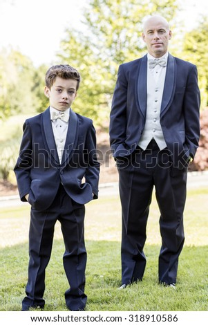 Father and son standing outside in formal wedding suits - stock photo