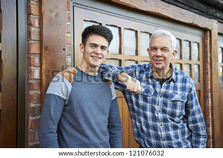 father and son standing together outside garage looking and smiling at camera - stock photo