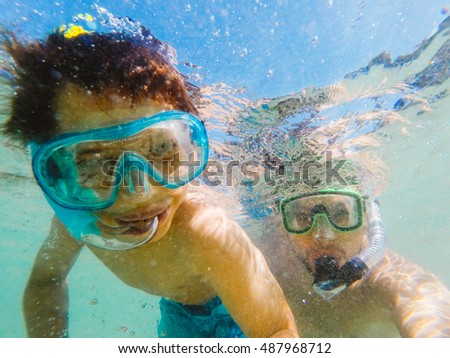 Father and son swimming together underwater