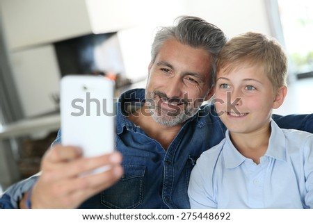 Father and son taking picture of themselves with smartphone - stock photo