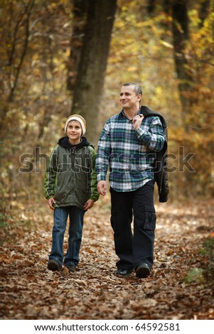 Father and son talking a walk outdoor in a forest, in an autumn day - stock photo