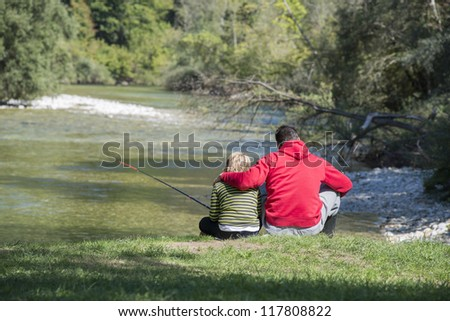 Father and son together fishing - stock photo