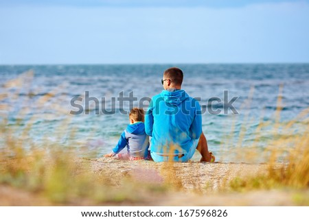 father and son together near the seaside - stock photo