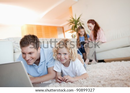 Father and son together with laptop on the floor - stock photo