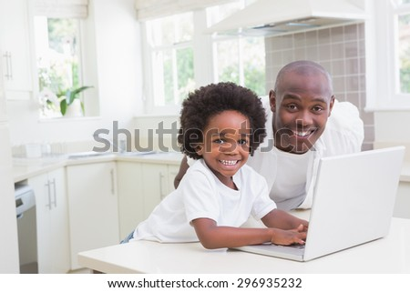 Father and son using laptop on the couch at home in living room
