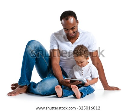 Father and son using tablet computer. Learning and early education concept / photos of Hispanic man and mixed race boy over white background - stock photo