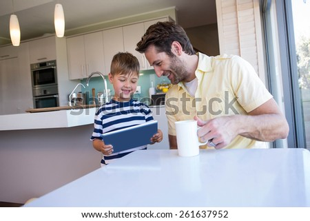 Father and son using tablet pc in the living room at home - stock photo