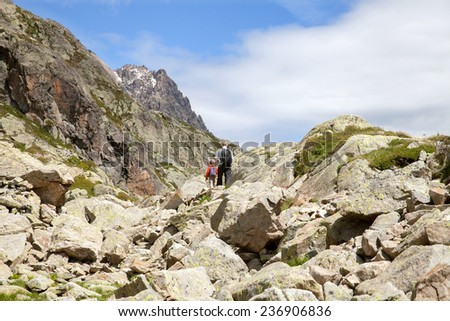father and son walking along a trail in the mountains - stock photo