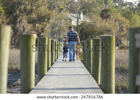 father and son walking down dock with crab trap - stock photo