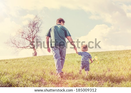 Father and son walking hand in hand up a hill in the spring - stock photo