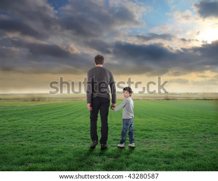 father and son walking in a grass field - stock photo
