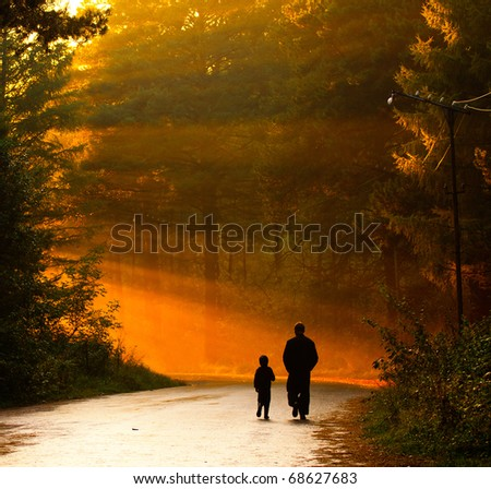 father and son walking in the sunlight - stock photo