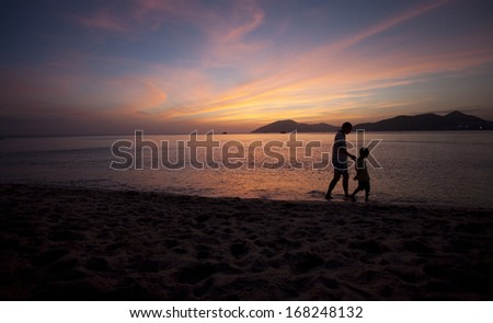 father and son walking on beach in sunset