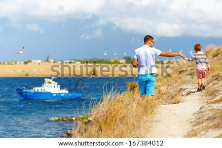 father and son walking on the cliff, seaside - stock photo