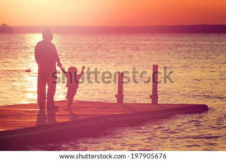 Father and son walking out on a dock at sunset - stock photo