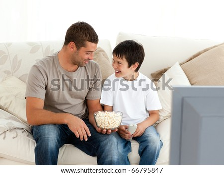 Father and son watching television while eating pop corn on the sofa at home