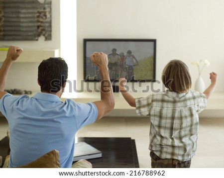 Father and son watching TV. - stock photo