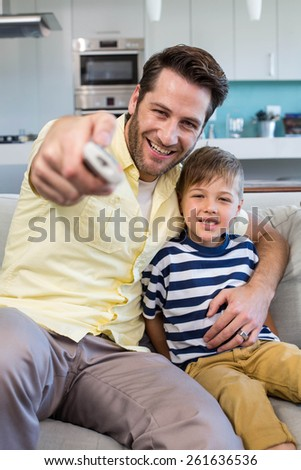 Father and son watching tv together on the couch at home in the living room - stock photo