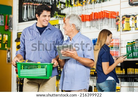 Father and son with digital tablet buying tools in hardware store with female customer in background