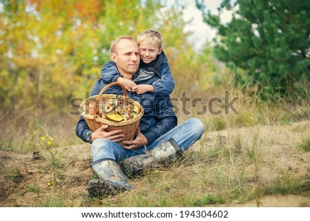 Father and son with full basket of mushrooms on the forest glade - stock photo