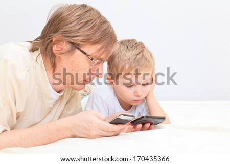 father and son with mobile phones at home, family communication - stock photo