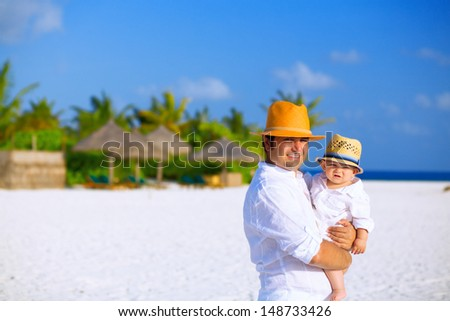 Father and son with panama hats stands on white sandy beach - stock photo