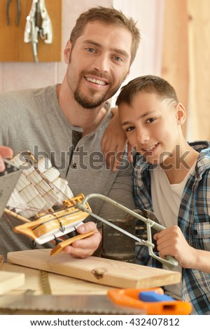 father and son with toy ship - stock photo