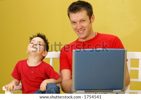 Father and son working on laptop together. - stock photo