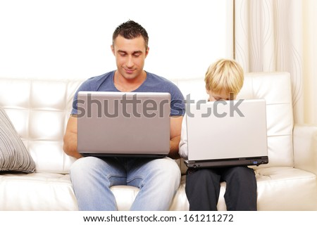 Father and son working on their computers on the sofa at home - stock photo