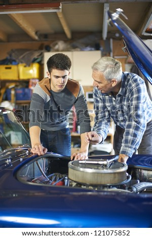 father and son working together on a classic car in a garage - stock photo