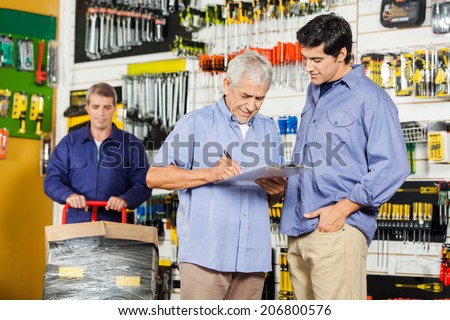 Father and son writing on checklist while worker working in background at hardware store - stock photo