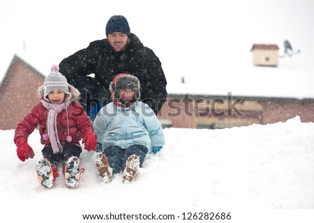 Father and sons having fun on the snow. - stock photo