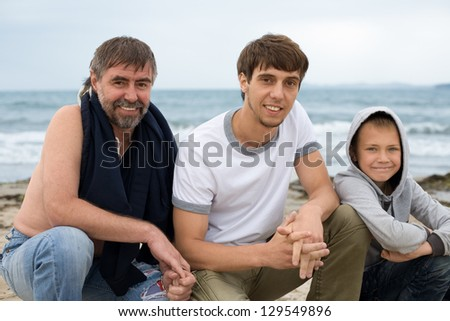 Father and sons on the beach on a summer day.