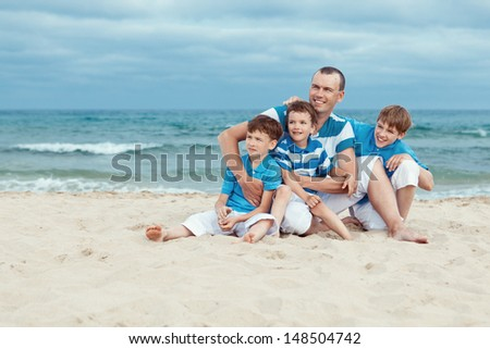 Father and sons sitting on sea - stock photo