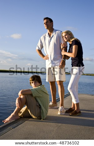 Father and teenage children on dock by water enjoying sunny day