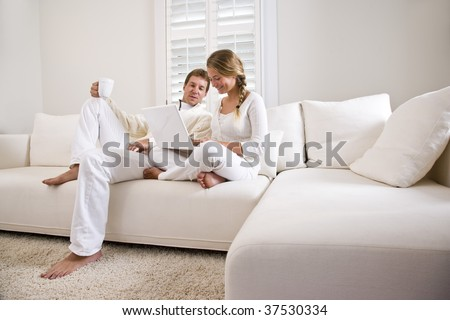 Father and teenage daughter on white living room sofa using laptop