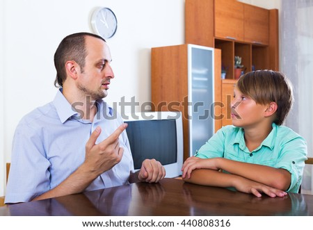 Father and teenager discussing something serious in living room at home - stock photo